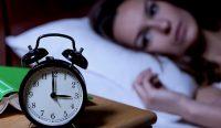 Bild eines Weckers neben einer Wachen Frau